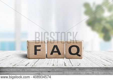 Faq Answers And Questions Sign Made Of Wooden Blocks. Standing On A Table In A Bright Living Area.