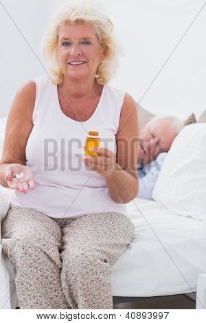 Old woman with an opened pill bottle with a man sleeping on the bed