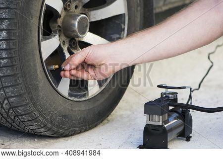 Car Compressor Wheel Pump. A Man Sits By A Car And Holds A Compressor For Inflating Car Tires, Close