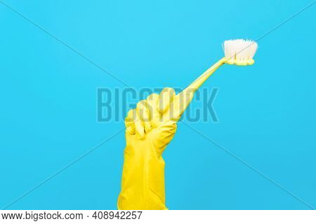 Hand In Yellow Rubber Glove Holding Brush For Cleaning On Blue Background. Household Cleaning Equipm