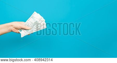 Senior Woman's Hand Holding Out Money On A Blue Background Indoors, Copy Space. Thousands Of Rubles.