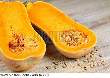Pumpkin Butternut Liscia Cut In Half. Yellow Delicious Pumpkin On Wooden Table, Seeds Around.