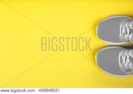 Gray Sneakers On A Yellow Background Sport Concept, Free Space.