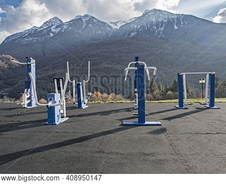 Workout Equipment In Outdoor Fitness Gym In Parkland At Mountains Background