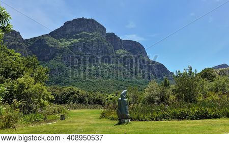 A Picturesque Mountain Rises Against The Backdrop Of A Blue Sky. At Its Base Is A Lawn With Green Gr