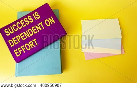 The Text Success Depends On Effort Is Written On A Colored Notebook That Lies On A Yellow Background