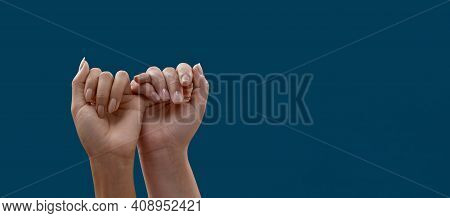 Two Hands Hook Each Other Little Finger Pinkie As A Symbol Of Promise Or Pardon Isolated On Blue Bac