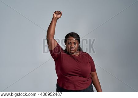 Portrait Of Fierce Plus Size Young African American Woman In Casual Clothes Looking At Camera, Stand