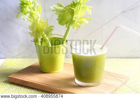 A Glass Of Celery Juice And A Green Bucket Of Celery.