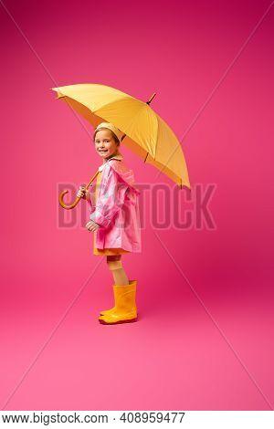Full Length Of Pleased Girl In Raincoat And Rain Boots Standing Under Umbrella On Crimson.