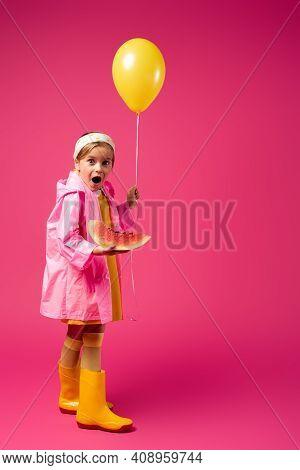 Full Length Of Amazed Girl In Raincoat Holding Balloon And Sliced Watermelon On Crimson.