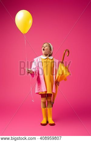 Full Length Of Amazed Girl In Raincoat And Rubber Boots Holding Balloon And Yellow Umbrella On Crims