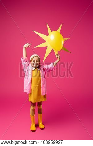 Full Length Of Excited Girl In Raincoat And Rubber Boots Holding Decorative Sun With Balloon On Crim