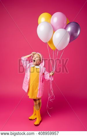 Full Length Of Surprised Girl In Raincoat And Rubber Boots Holding Balloons On Crimson.