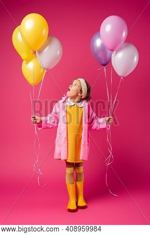Full Length Of Amazed Girl In Raincoat And Rubber Boots Holding Balloons On Crimson.
