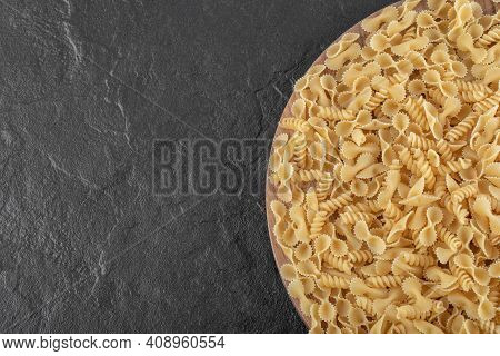 Raw Wholewheat Pasta On Dark Marble Background