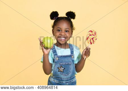 Little African Child Girl Holds Sweet Lollipop And Fresh Green Apple, Smiling To Camera On Yellow Ba