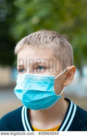 Blonde Caucasian Boy 7 8 Years Old In A Cozy Warm Sweater And In Protective Medical Mask On The Stre