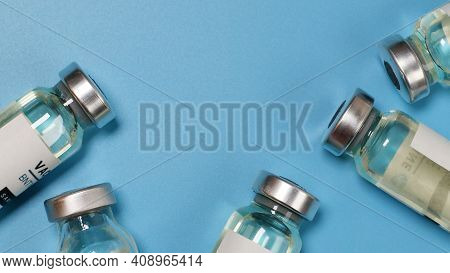 Coronavirus Covid-19 Experimental Vaccine Vials On A Blue Plate With Copyspace In A Laboratory. Vacc