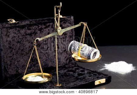 Weighing scales with wad of dollars and white powdered drug beside big pile of drug