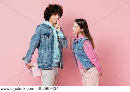 Teenager Showing Shh Gesture While Hiding Present Near Girlfriend On Pink Background.