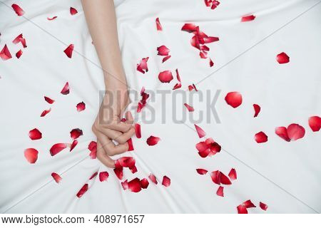 Women Hand Pulling Or Grasping White Sheets. Hand Sign Orgasm Of Woman On White Bed Sheet With Rose