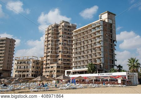 Famagusta, Cyprus - September 15 2016: Palm Beach With Beach Umbrellas And Tourists And The Abandone