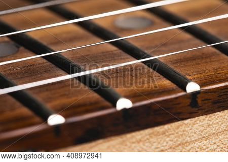 Close-up Of An Electric Guitar Neck With Wood Frets And Strings. Music Background