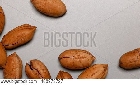 Assorted Pecan Nuts In Shell On Gray Background With Copy Space