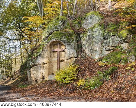 Wooden Cross At Sandstone Rock Niche Along Country Road At Colorful Autumn Deciduous Beech Tree Fore
