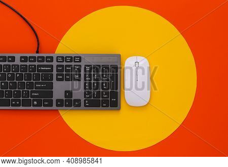 Pc Keyboard And Pc Mouse On Orange Background With Yellow Circle. Top View