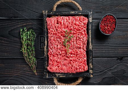 Raw Mince Ground Beef And Pork Meat In A Wooden Tray With Herbs. Black Background. Top View