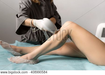 Beautician Removing Hair On Slim Female Legs Using A Laser. Hair Removal, Laser Procedure At Clinic.