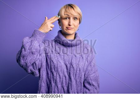 Young blonde woman with short hair wearing winter turtleneck sweater over purple background Shooting and killing oneself pointing hand and fingers to head like gun, suicide gesture.