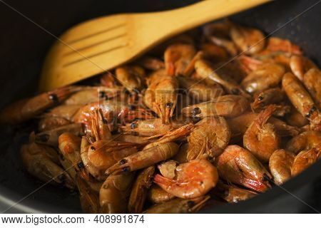 Grilled Fresh Shrimp, Fried With Spices And Butter. Close-up Of Fried Shrimp And Wooden Spatula In A