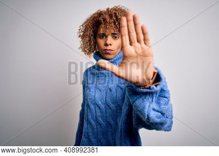 Young beautiful african american woman wearing turtleneck sweater over white background doing stop sing with palm of the hand. Warning expression with negative and serious gesture on the face.