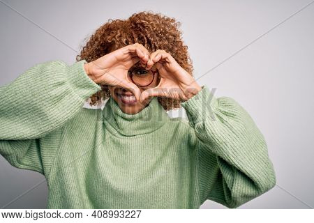 Young beautiful african american woman wearing turtleneck sweater and glasses Doing heart shape with hand and fingers smiling looking through sign