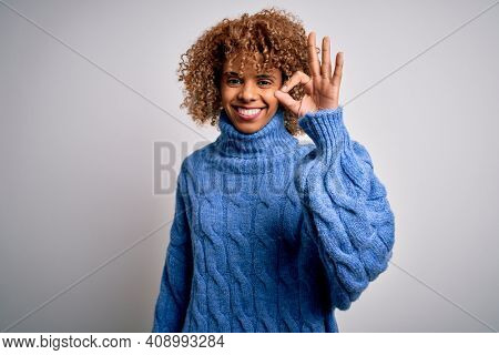 Young beautiful african american woman wearing turtleneck sweater over white background smiling positive doing ok sign with hand and fingers. Successful expression.
