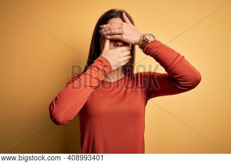 Young beautiful brunette woman wearing casual t-shirt standing over yellow background Covering eyes and mouth with hands, surprised and shocked. Hiding emotion