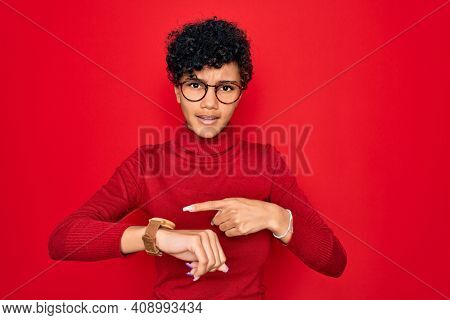 Young beautiful african american afro woman wearing turtleneck sweater and glasses In hurry pointing to watch time, impatience, upset and angry for deadline delay