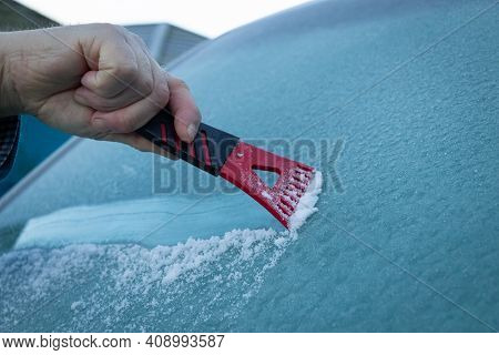 A Man Scraping Ice Off A Frozen Wind Shield Or Screen Of A Vehicle On A Cold Winters Morning