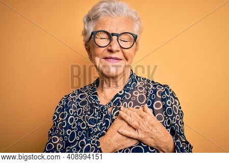 Senior beautiful grey-haired woman wearing casual shirt and glasses over yellow background smiling with hands on chest with closed eyes and grateful gesture on face. Health concept.
