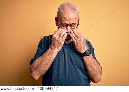 Middle age handsome hoary man wearing casual polo and glasses over yellow background rubbing eyes for fatigue and headache, sleepy and tired expression. Vision problem