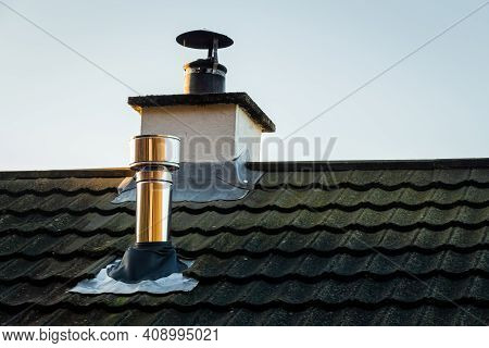 Modern Metal Wood Burning Stove Chimney On A Grey Slate Roof With The Original Chimney