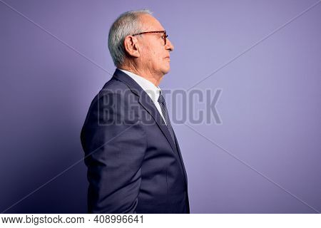 Grey haired senior business man wearing glasses and elegant suit and tie over purple background looking to side, relax profile pose with natural face and confident smile.
