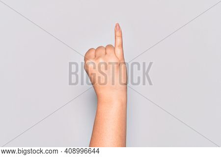 Hand of caucasian young woman showing little finger as pinky promise commitment, number one