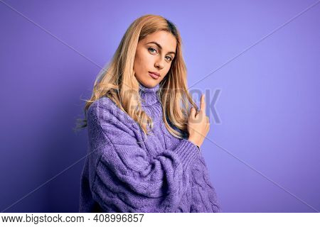 Young beautiful blonde woman wearing casual turtleneck sweater over purple background Pointing with hand finger to the side showing advertisement, serious and calm face