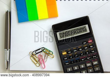 Onboarding Symbol. Calculator With The Word 'onboarding', White Note, Colored Paper, Paper Clips, Pe