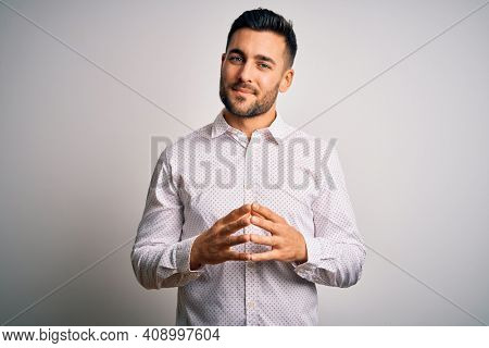 Young handsome man wearing elegant shirt standing over isolated white background Hands together and fingers crossed smiling relaxed and cheerful. Success and optimistic