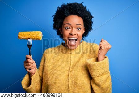 Young African American afro vegetarian woman with curly hair holding fork with cob corn screaming proud and celebrating victory and success very excited, cheering emotion